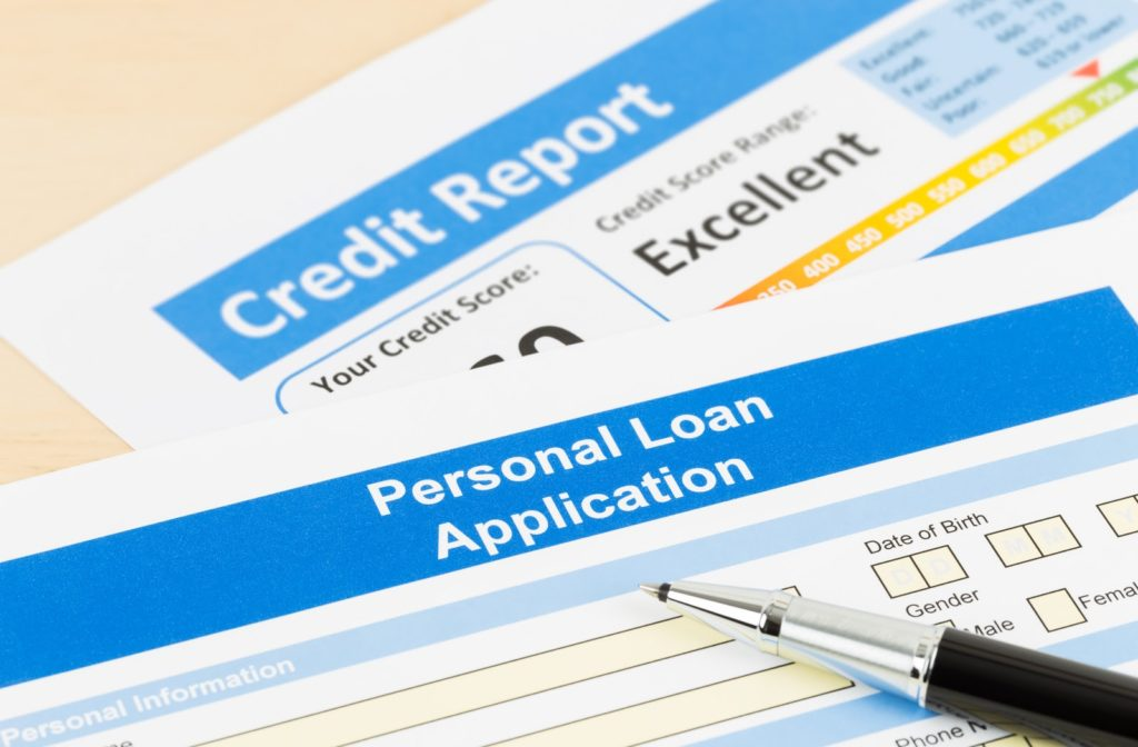 Pen lying on personal loan application next to credit check printout