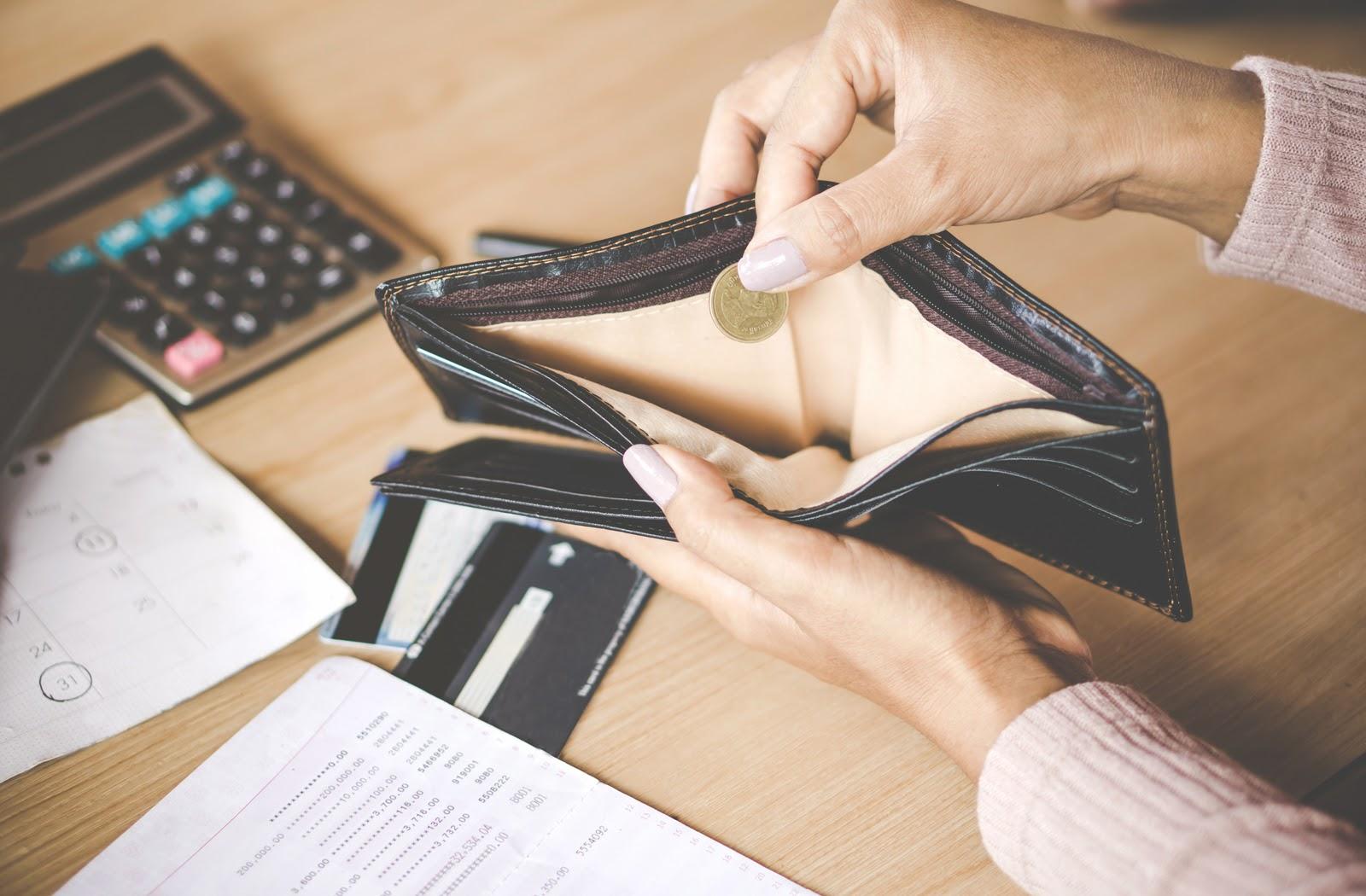 Woman looking into near-empty wallet, realizing she needs a loan.