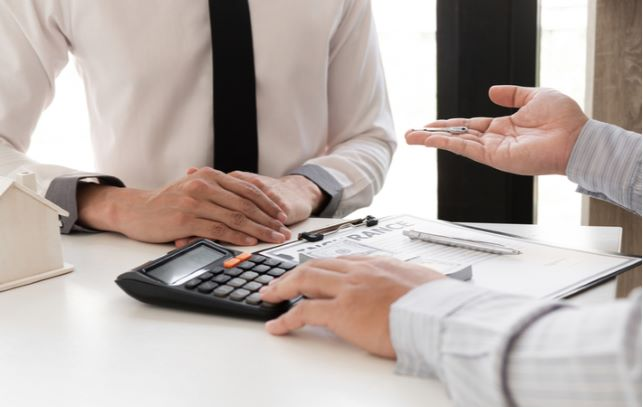 Advisor and client sitting together discussing loan while using calculator