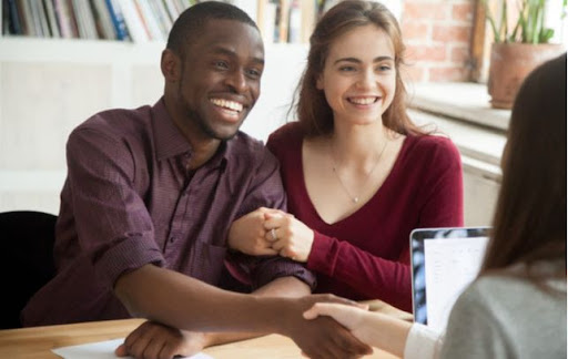 Young happy couple shaking hands with advisor after taking out loan